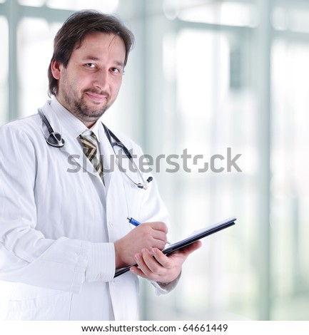 Closeup portrait of a happy young doctor with stethoscope in hospital writing a receipt - stock photo