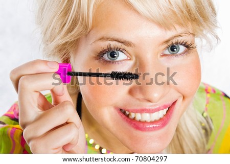 Closeup portrait of a happy young female applying mascara with brush - stock photo