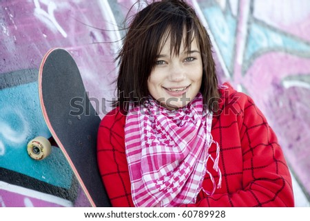 Closeup portrait of a happy young girl with skateboard and graffiti on background - stock photo