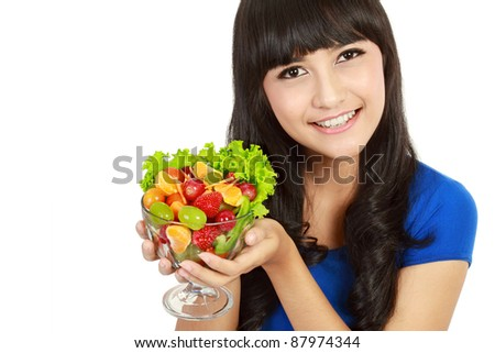 Closeup portrait of a happy young lady eating fruit salad, in white background