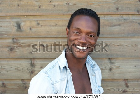 Closeup portrait of a happy young man smiling outdoors against wood background
