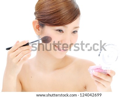 Closeup portrait of a happy young woman applying make up on her face - stock photo