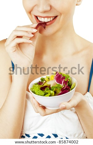 Closeup portrait of a happy young woman eating vegetarian salad - stock photo