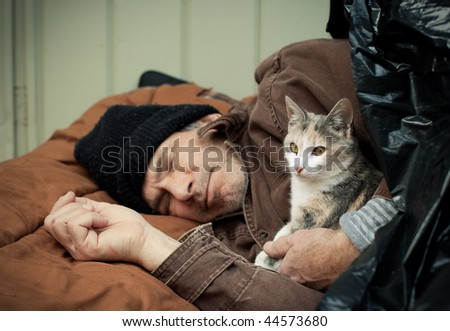Closeup portrait of a homeless older man sleeping under a plastic tarp on the street with a friendly stray kitten. Selective focus on the man's hands and the kitten. - stock photo