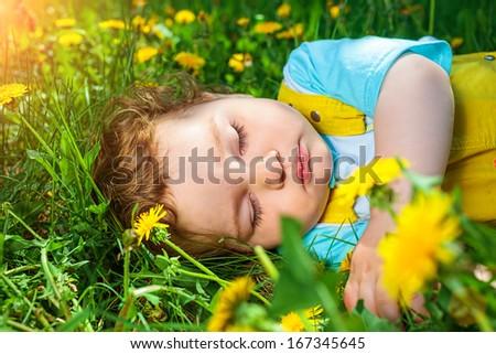 Closeup portrait of a little baby boy sleeping outdoors on grass. - stock photo