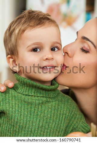 Closeup portrait of a little boy embracing his mother - stock photo