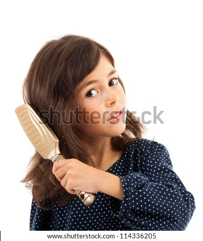Closeup portrait of a little girl brushing her hair isolated on white - stock photo