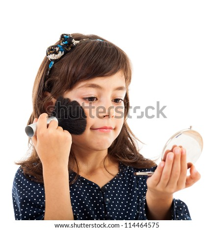 Closeup portrait of a little girl using face powder while looking in the mirror