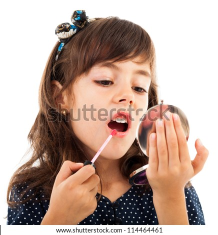 Closeup portrait of a little girl using lipstick while looking in the mirror - stock photo