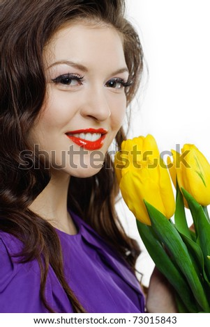 Closeup portrait of a lovely girl with yellow tulips against white background - stock photo