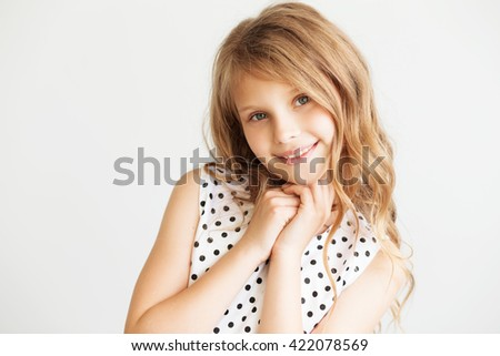 Closeup portrait of a lovely little girl against a white background - stock photo