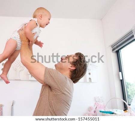 Closeup portrait of a loving father lifting and playing with cute baby - stock photo
