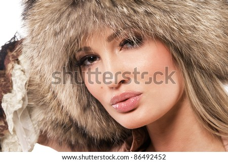 Closeup portrait of a magnificent woman in fur hat - stock photo