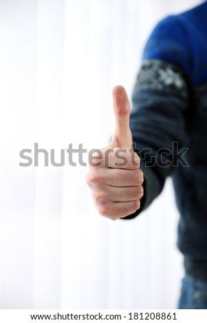 Closeup portrait of a male hand with thumb up