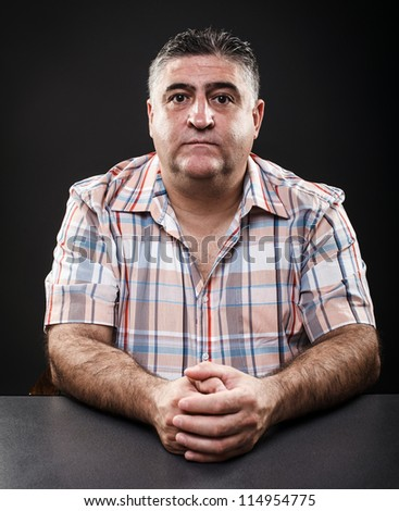 Closeup portrait of a mature man sitting at table on gray background - stock photo