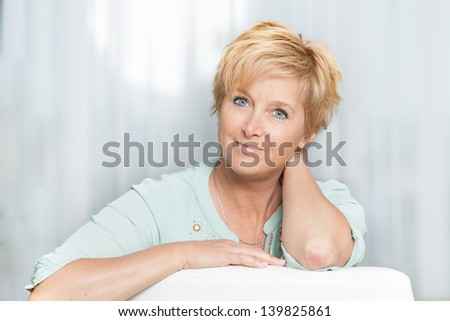 Closeup portrait of a mature woman at home looking at camera - stock photo