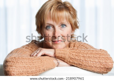 Closeup portrait of a mature woman at home looking at camera