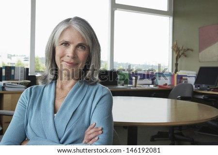 Closeup portrait of a middle aged businesswoman smiling in office - stock photo