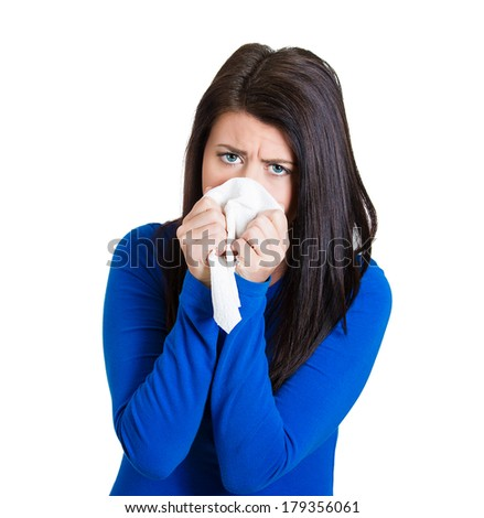 Closeup portrait of a miserable, sick teen woman with allergy, cold, blowing her nose with paper tissue, isolated on white background. Human face expressions. Flu season, vaccination, prevention. - stock photo