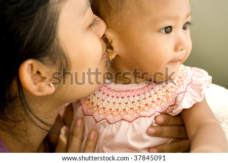 Closeup portrait of a mother kiss her baby girl - stock photo