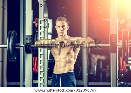 Closeup portrait of a muscular man workout with barbell at gym. Brutal bodybuilder athletic man with six pack, perfect abs, shoulders, biceps, triceps and chest - stock photo