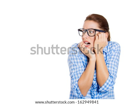 Closeup portrait of a nervous, young, beautiful woman wearing black glasses, biting her nails, craving for something, anxious or scared, looking away isolated on white background with copy space - stock photo