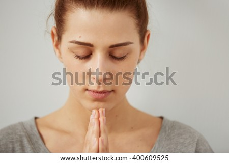 Closeup portrait of a peaceful woman praying. Sad woman prays holding clasp hands together, concept of girl problem, stress, depression. Human emotion facial expression body language. - stock photo