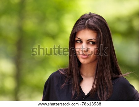 Closeup portrait of a pensive doubtful young woman outdoor in the forest - stock photo