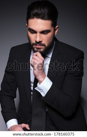 closeup portrait of a pensive young fashion man looking down, away from the camera while holding his hand on his chin. on a dark background