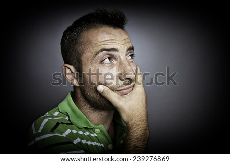 Closeup portrait of a perplexed man. Green eyes and hand under his chin. - stock photo