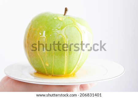 Closeup portrait of a plate with green apple covered with honey, isolated on white. Concept of healthy nutrition, beauty and diet - stock photo