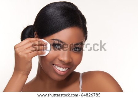 Closeup portrait of a pretty african young woman using cotton on her face - stock photo