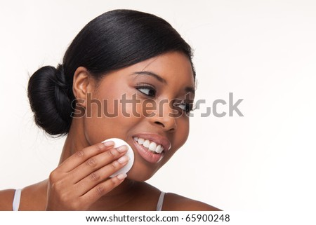 Closeup portrait of a pretty african young woman using cotton on her face - very sharp unretouched photo
