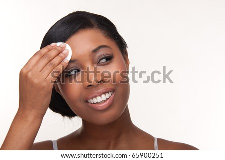 Closeup portrait of a pretty african young woman using cotton on her face - very sharp unretouched photo - stock photo