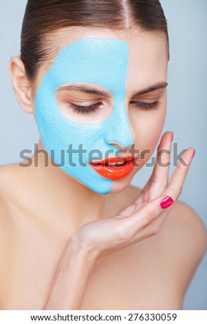 Closeup portrait of a pretty woman with a blue clay mask - stock photo