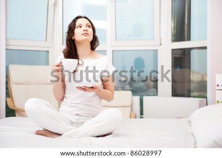 Closeup portrait of a pretty young female having a cup of coffee and daydreaming while sitting relaxed in lotus pose on bed at home