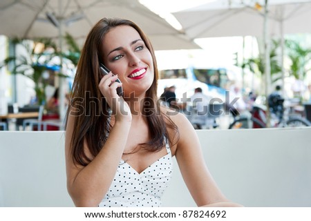 Closeup portrait of a pretty young female sitting at cafe in morning and talking phone - stock photo