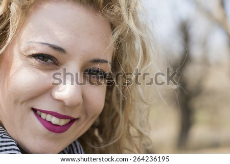 Closeup portrait of a pretty young woman with blond curly hair smiling direct to the camera