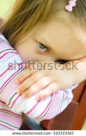 closeup portrait of a sad little girl outdoors - stock photo