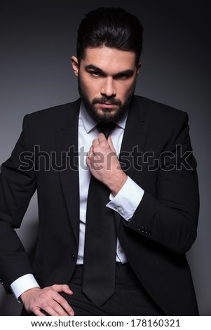 closeup portrait of a seated young fashion man arranging his tie while looking into the camera with a serious expression. on a dark background