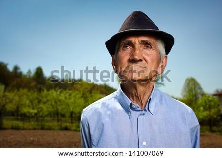 Closeup portrait of a senior farmer outdoor - stock photo