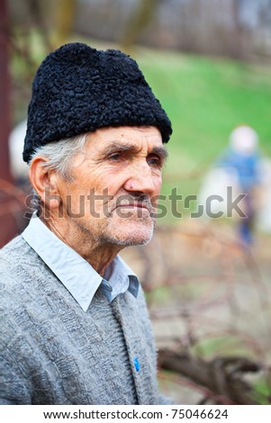 Closeup portrait of a senior farmer with woolly hat outdoor - stock photo