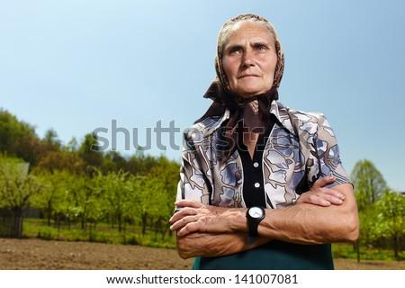 Closeup portrait of a senior farmer woman outdoor - stock photo