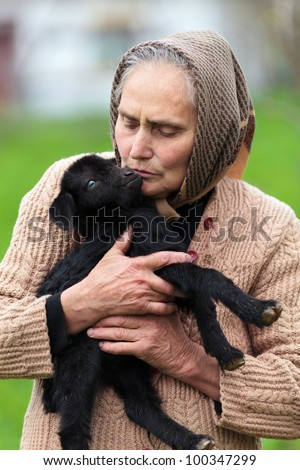 Closeup portrait of a senior woman holding a baby goat outdoor
