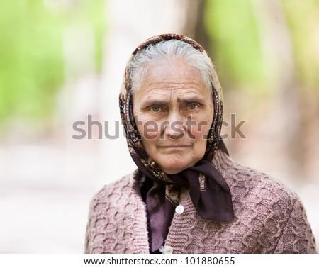 Closeup portrait of a senior woman with kerchief outdoor - stock photo