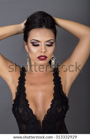 Closeup portrait of a sensual brunette woman posing in sexy black lingerie over gray background - stock photo