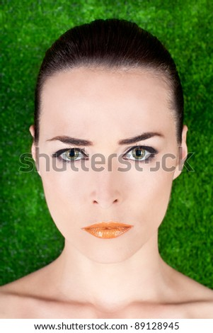 Closeup portrait of a serious angry beautiful woman with green eyes and glossy lips on green background - stock photo