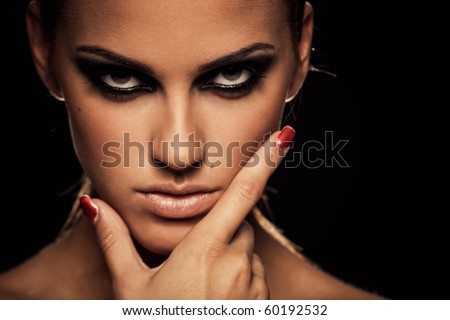 Closeup portrait of a serious lady with smoky eye makeup - stock photo