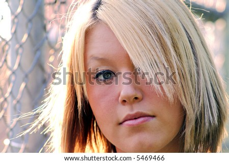 Closeup portrait of a serious young blond woman, taken outdoors.  Horizontal format. - stock photo