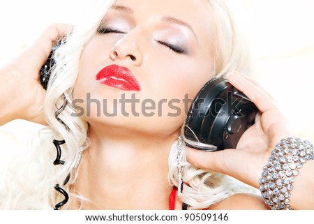 closeup portrait of a sexy beautiful woman posing in headphones over white - stock photo